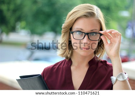 Serious Young Business Woman Wearing Eye Glasses Looking at the Camera - stock photo