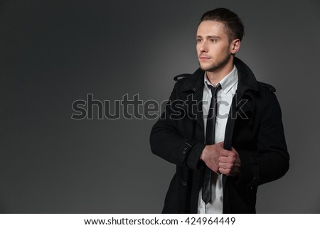 Serious young businessman in black coat, white shirt and tie standing  over grey background