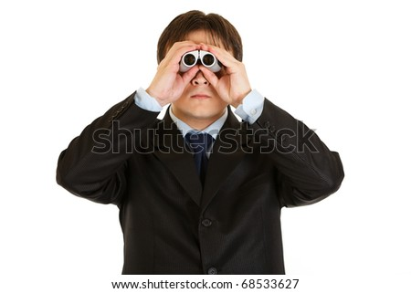 Serious young businessman looking through binoculars isolated on white