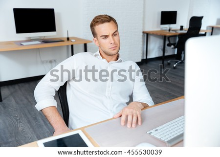 Serious young businessman sitting at workplace and using computer in office