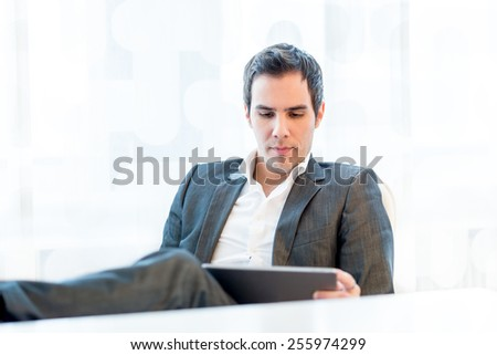 Serious young businessman sitting in his chair at his desk with his feet up reading his tablet-pc - stock photo