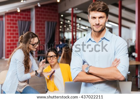 Serious young businessman standing with arms crossed with his colleagues talking and working on background