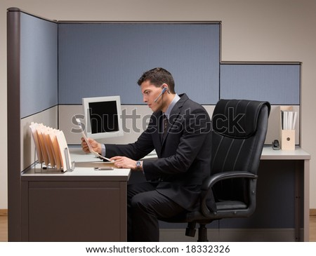 Serious young businessman with headset working at desk in cubicle - stock photo