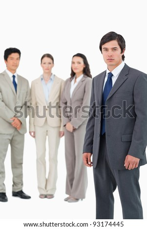 Serious young businessman with team behind him against a white background