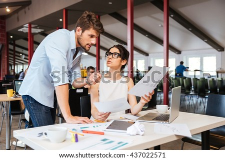 Serious young businesspeople discussing business plan in office together - stock photo