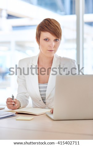 Serious young businesswoman at her desk with laptop