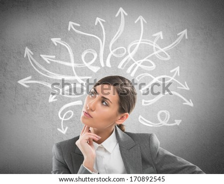 Serious, young businesswoman looking at many twisted arrows on the concrete wall overhead - stock photo