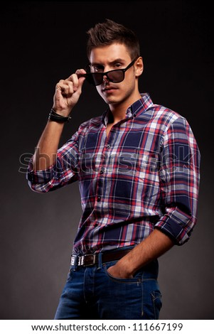 Serious young casual man taking down his sunglasses. Young casual man looking at the camera over his sunglasses . On black background. - stock photo