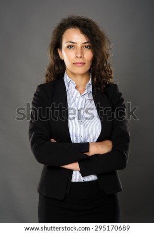 Serious young caucasian businesswoman with arms folded - stock photo