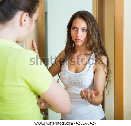 Serious young females having conflict at the door