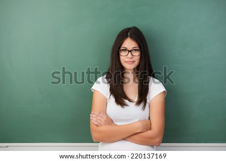 Serious young girl wearing glasses in class at college standing with her back to a blank chalkboard looking at the camera with folded arms, copyspace to the side - stock photo