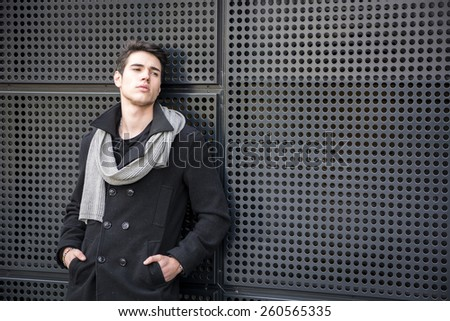 Serious Young Handsome Man in Winter Outfit Leaning on a Metal Wall While Looking to the Right of the Frame at Large Copyspace - stock photo