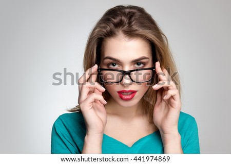 Serious young lady in glasses and with red lips looking at the camera in studio on grey background