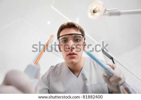 Serious young male holding dental tools with man in the background