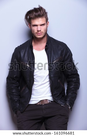 serious young man in leather jacket standing against gray wall looks at the camera