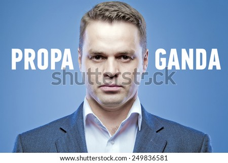 Serious young man on a blue background with the words: Propaganda - stock photo