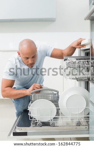 Serious young man using dish washer in the kitchen at home