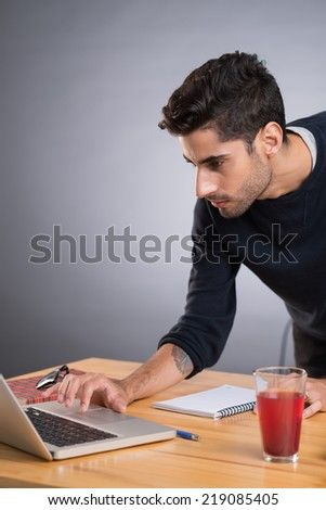 Serious young man using laptop - stock photo