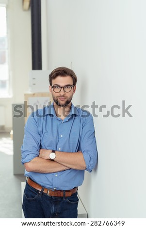 Serious young man wearing casual blue shirt, brown leather belt, jeans, wristwatch and black frame eyeglasses while standing with folded arms leaning on a white wall and looking at camera - stock photo
