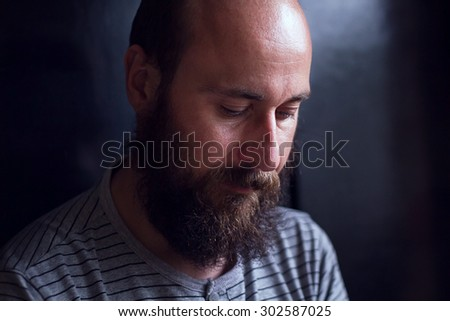 Serious young man with a beard looking down. Close up image with shallow depth of field - stock photo
