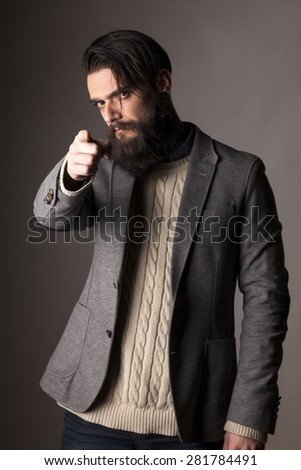 serious young man with a long beard pointing on you - stock photo
