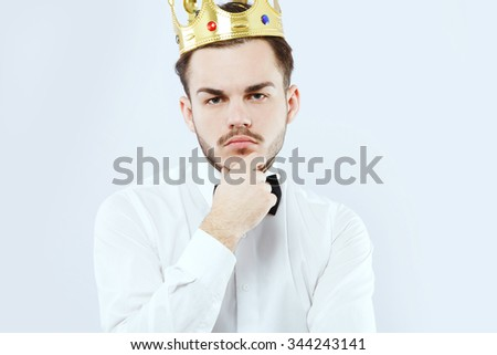 Serious young man, with beard and mustaches, wearing in white shirt, bow and gold crown, posing like he is thinking, on white background and looking at camera, in studio, waist up - stock photo