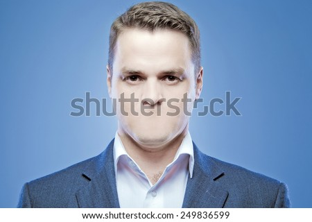 Serious young man without a mouth on a blue background  - stock photo