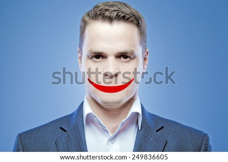 Serious young man without a mouth on a blue background with false smile - stock photo