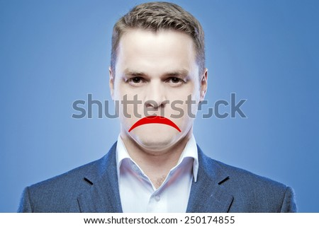 Serious young man without a mouth on a blue background with the false sad smile - stock photo