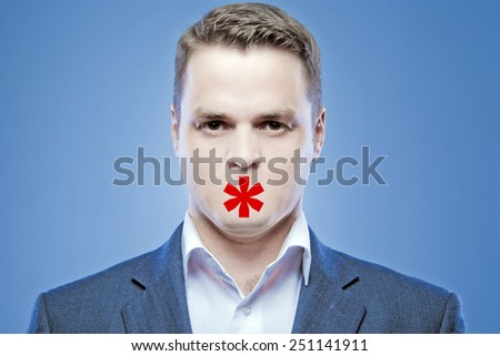 Serious young man without a mouth on a blue background with the sign of kiss - stock photo