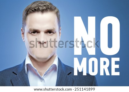Serious young man without a mouth on a blue background with the words: No More - stock photo