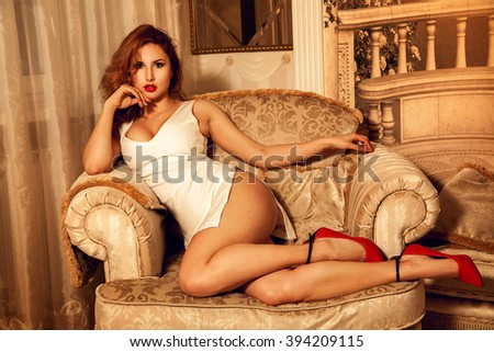 Serious young sexual lady in white dress posing on chair and looking at camera. Seductive woman. Sexual woman. the concept of seduction, pleasure and desire - stock photo