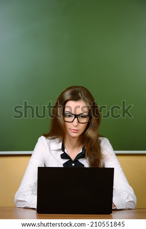 Serious young teacher in spectacles sitting at a desk with a laptop. Education.