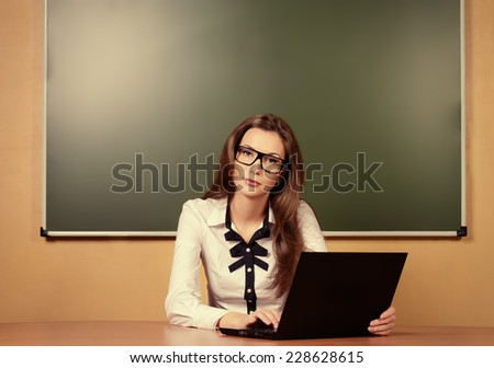 Serious young teacher in spectacles sitting at a desk with a laptop. Education. - stock photo