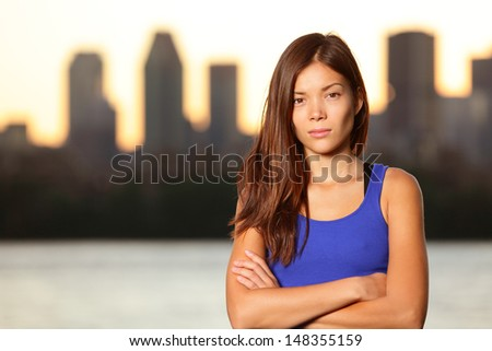 Serious young urban girl portrait in city with skyline in background. Young woman looking at camera intense. Multiracial Asian Chinese / Caucasian female model. - stock photo