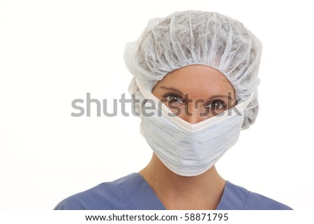Serious young woman doctor in scrubs with mask and cap - stock photo