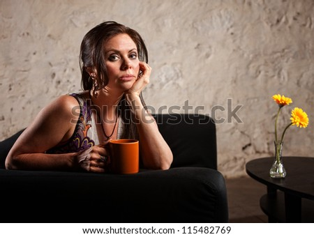 Serious young woman holding coffee mug sitting near table - stock photo
