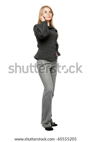 Serious young woman in a gray business suit talking on the phone - stock photo