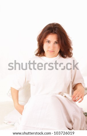 Serious young woman in bed - stock photo