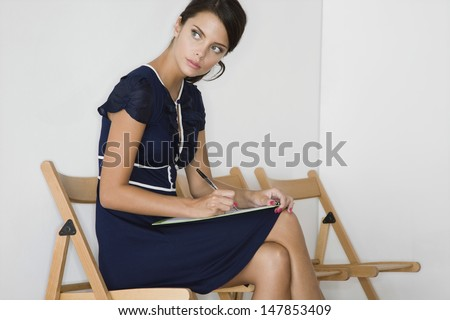 Serious young woman in blue dress writing at waiting room