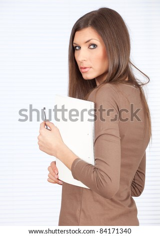 serious young woman in brown blouse keeping red clipboard - stock photo