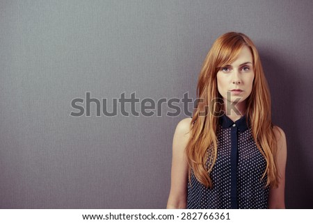 Serious Young Woman in Sleeveless Shirt, with Long Blond Hair, Against Gray Wall Background with Copy Space and Looking at the Camera. - stock photo