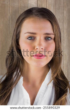 Serious young woman in white shirt against wooden surface with planks - stock photo