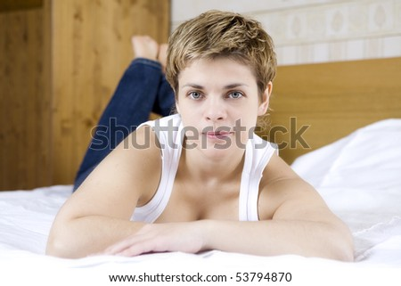 serious young woman in white with manicure lying on bed