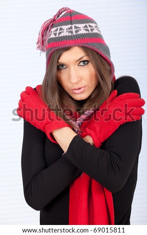 serious young woman in winter cap and mittens with hands on shoulders - stock photo