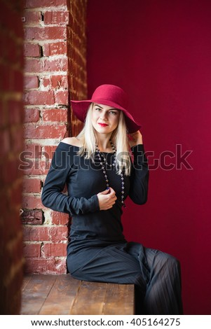 Serious young woman sitting on a windowsill with a hat red lips lipstick look a serious sadness color. a psychological portrait, looking right - stock photo