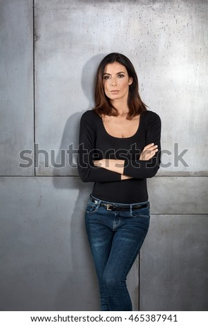 Serious young woman standing against wall arms crossed, looking at camera.
