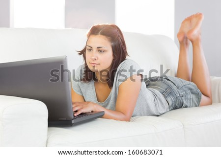 Serious young woman using her notebook while lying on her couch in the living room at home - stock photo