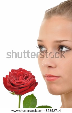 Serious young woman with a rose full of water drops - stock photo