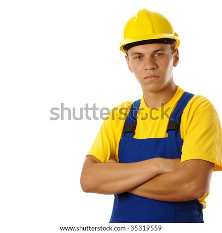 Serious young worker wearing hard hat and blue-and-yellow uniform, isolated over white - stock photo